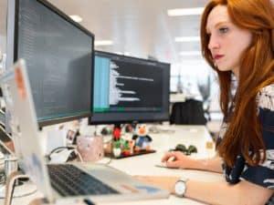 Imagem de uma mulher usando o computador em um escritório. Usamos para ilustrar o post sobre a segunda fase do open banking