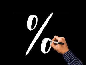 em um fundo preto, aparece uma mão com uma caneta desenhando um símbolo de porcentagem em branco para representar a taxa média de juros