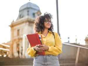 Imagem de uma estudante em sua faculdade segurando cadernos em suas mãos. Usamos a foto para ilustrar a notícia sobre a abertura de vagas para estágios e trainee