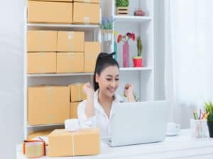 imagem para ilustrar o artigo sobre vender mais com uma mulher olhando para o computador sorrindo e com caixas próximas a ela