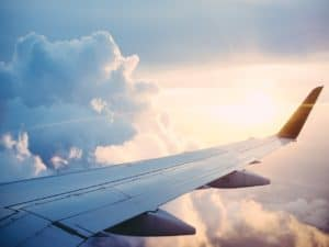na imagem tem uma asa de avião em meio às nuvens