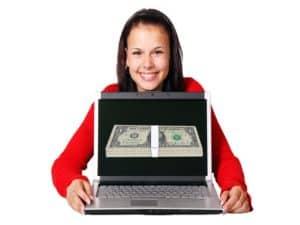 mulher aparece sorrindo e abrindo um notebook e na tela surge uma pilha de notas de dólares