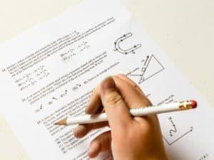 A imagem mostra uma mão com um lápis e uma prova na mesa representando um dos concursos públicos disponíveis