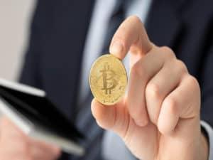 homem segura um celular em uma mão e uma moeda com o símbolo do bitcoin na outra, representando ETF de criptomoedas