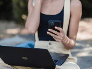 Imagem de uma pessoa usando um computador e um celular para entender como ganhar dinheiro com cartão de crédito