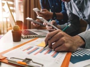 Imagem para simbolizar a gestão de negócios de uma pessoa fazendo anotações numa página com gráficos