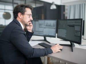 Imagem de um homem usando o computador em um ambiente empresarial, lendo alguma informação na tela. Usamos a foto para ilustrar nosso conteúdo sobre golpes de pirâmide