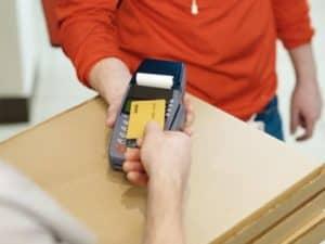 imagem de uma pessoa pagando com uma máquina de cartão que o dinheiro cai na hora