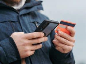 Imagem de uma pessoa segurando um cartão de crédito e um celular na mão, ilustrando o post sobre a maquininha virtual da Stone