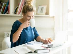 imagem de uma mulher tomando café e usando o notebook para ilustrar o conteúdo sobre negócios lucrativos