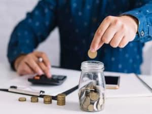 homem fazendo as contas com moedas procurando onde investir com pouco dinheiro