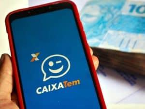 mão segurando celular com interface do app Caixa Tem representando programa de microcrédito Caixa.