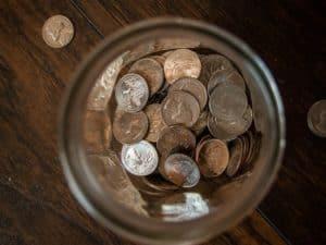 Imagem de várias moedas em um pote, representando a notícia que divulgou que o valor do Auxílio Brasil, o novo Bolsa Família, será de R$ 300