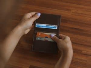 Imagem de uma carteira com alguns cartões de crédito nas mãos de uma mulher. Foto usada para ilustrar o post sobre como ter cartão aprovado na hora