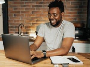 conta mei santander: imagem de um homem utilizando um notebook em uma mesa