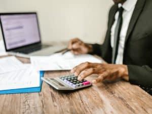 imagem de um homem usando uma calculadora com papéis e computador na mesa para representar um pedido de empréstimo para empresa negativada