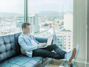 imagem de um homem sentado num sofá com o computador no colo para ilustrar o artigo sobre empréstimo para empresa online