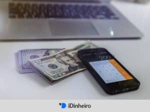 notas de dólar, celular e computador, representando investimento no exterior