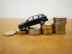 imagem de uma miniatura de carro em cima de pilhas crescentes de moedas