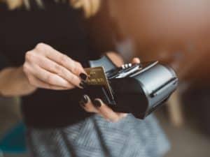 Imagem de uma mulher passando um cartão em uma maquininha de vendas. Foto usada para ilustrar a lista com os melhores cartões de crédito em 2021
