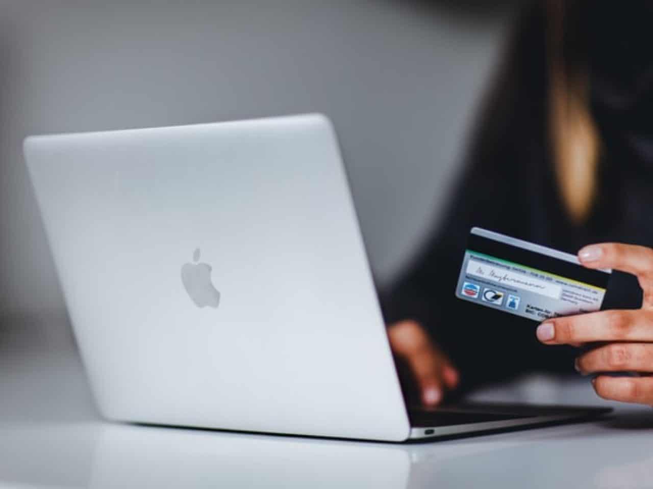 imagem de uma pessoa usando o notebook com um cartão de crédito na mão para simbolizar os melhores gateways de pagamento