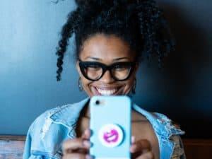 Imagem de uma mulher sorrindo enquanto segura um telefone celular. Usamos a imagem para ilustrar o post sobre melhores seguros para celular