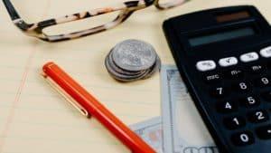 uma caneta, uma calculadora, notas e moedas e um óculos em cima da mesa
