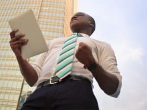 imagem de um homem com um tablet numa mão em frente a um prédio para ilustrar o artigo sobre o que é microcrédito