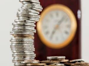uma pilha de moedas, ao fundo, um relógio desfocado