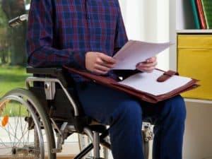 Cadeirante com papelada em mãos, representando auxílio inclusão.