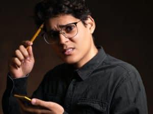 Homem jovem, com olhar preocupado, segurando um bloco de anotações e coçando a cabeça com uma lapiseira