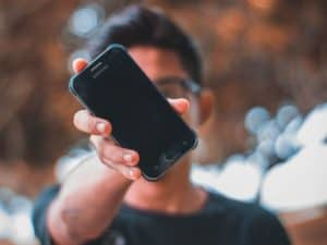 Homem jovem segurando um celular na frente do rosto, representando a contratação do empréstimo Crédito Caixa Tem via smartphone