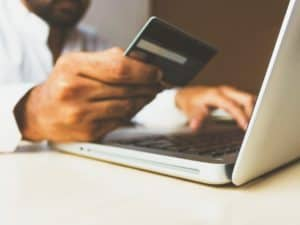 Imagem de um homem segurando um cartão de crédito cinza e digitando em um notebook com a outra mão. Foto usada para ilustrar nosso post sobre o cartão de crédito com maior limite do mundo