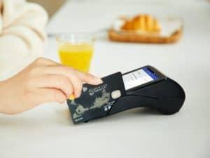 Imagem de uma mão segurando um cartão de crédito enquanto passa o objeto em uma maquininha de pagamento. Ambos estão na cor preta. Imagem usada para ilustrar o conteúdo sobre cartão de crédito para score baixo.
