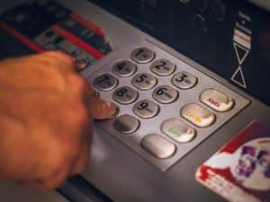 Imagem centralizada em uma mão digitando algo parecido como a senha de um cartão de crédito. O zoom está centralizado em um caixa eletrônico de banco. Foto usada para ilustrar um conteúdo sobre como sacar dinheiro do cartão de crédito.