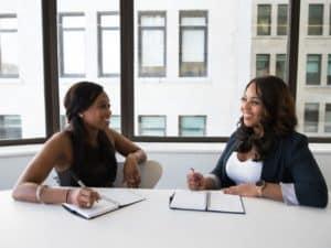 imagem de duas mulheres conversando em uma mesa de reuniões para ilustrar o artigo sobre conta mei bradesco