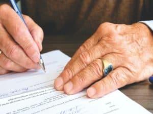 mãos de um homem mais velho assinando um documento