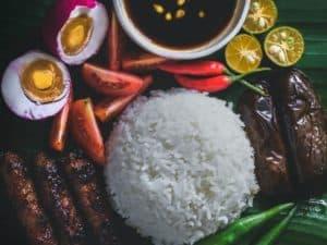 arroz, legumes, carnes e outros alimentos variados sobre uma mesa, representando o aumento do preço dos alimentos causado pelo crise hídrica