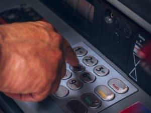 mão digitando números em um caixa eletrônico, representando depósito com envelope