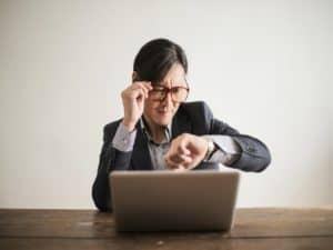 homem sentado na frente de um notebook segurando os óculos no rosto e olhando as horas no relógio