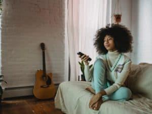imagem de uma mulher com um controle de televisão na mão para assistir filmes de empreendedorismo