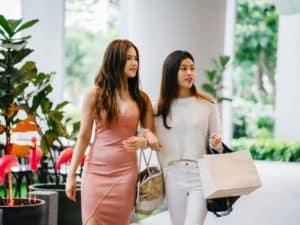 frases para atrair clientes: imagem de duas mulheres com sacolas e bolsas considerando entrar numa loja