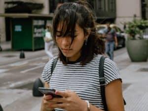 Mulher olhando para celular, representando golpes em novas formas de transferência bancária