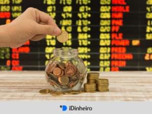vidro com moedas e painel de cotação ao fundo representando investimento em ações para iniciantes