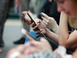 Foto de uma série de mãos segurando celulares, o foco está nas mãos e não mostra o rosto das pessoas. Foto usada para ilustrar o post sobre pedir crédito emprestado na Vivo