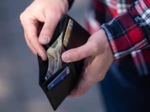 Mão de um homem branco segurando uma carteira entreaberta, representando score mínimo para cartão de crédito. Dentro da carteira é possível ver cartões de crédito e notas de dinheiro.