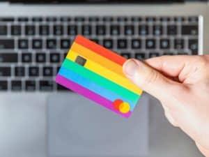 Imagem focada em uma mão que está segurando um cartão de crédito colorido em suas mãos. Em segundo plano, vemos o teclado de um notebook. A foto foi usada para ilustrar o conteúdo sobre tipos de cartão de crédito.